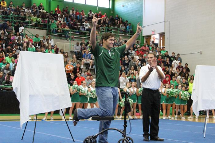 Luke Joeckel holds his horseshoes high as the crowd roars. Joeckel's high school jersey, No. 72, was retired.