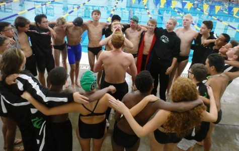 Seniors Austin Whitley and Dylan Nash lead the swim team in a team cheer before the start of the races.