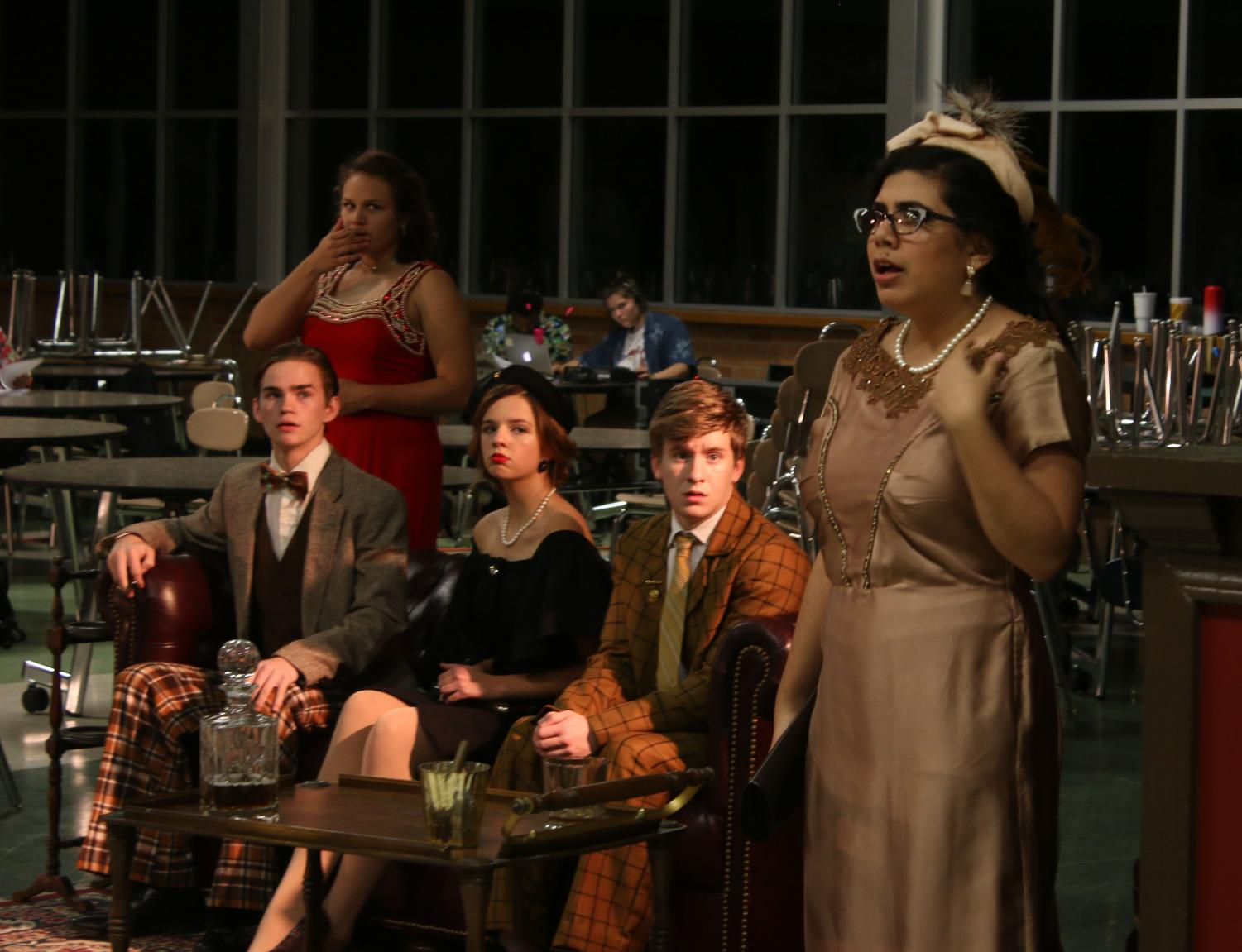 Mrs. Peacock, played by senior Gloria Adame, reacts to shocking news while the rest of the characters look on.