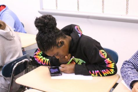 A student uses her phone during math class to watch a video to further her understanding of the assignment.